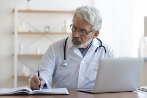 Serious mature doctor wearing glasses working with medical documents and laptop, sitting at desk in hospital, busy senior therapist practitioner gp writing illness history, filling patient card